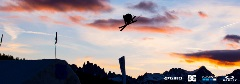 Skier flying off a jump in the Unbound Main Park with a Sierra sunset background.