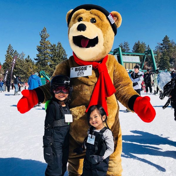 two kids taking a photo with biggie the bear