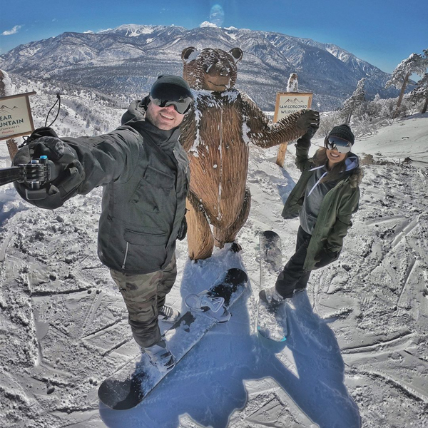 two snowboarders taking a selfies with a bear status on top of a mountain