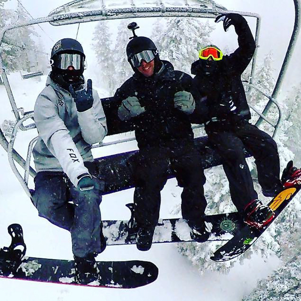 three guys posing for a selfie on a chairlift in the snow