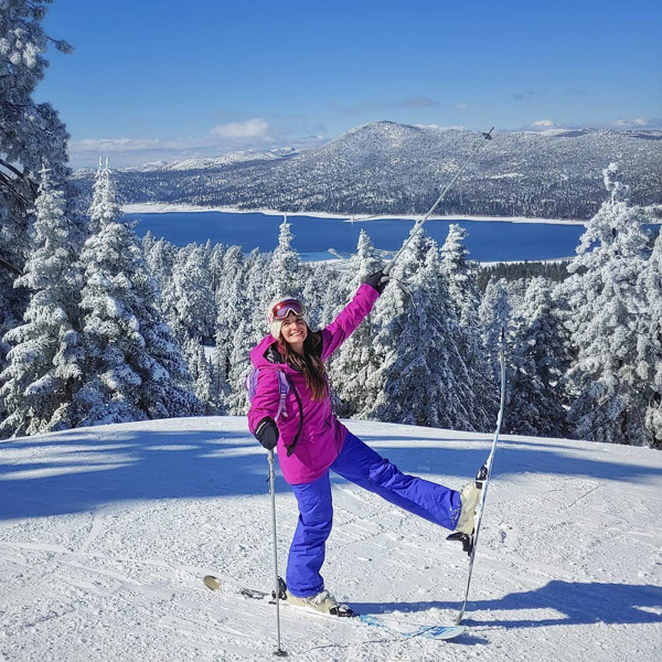 skier posing for a photo with snow covered big bear lake in the background